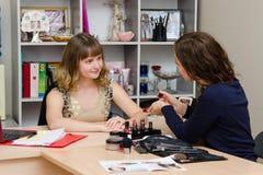 Le maquilleur montre au client un nouveau rouge à lèvres Images libres de droits