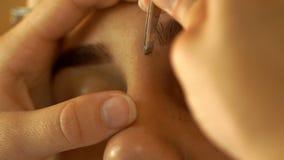 Le maquilleur professionnel fait des brucelles de sourcil de correction banque de vidéos