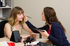 Le maquilleur s'appliquent le maquillage à l'employé de bureau de cils Photographie stock libre de droits