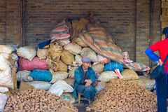 Le marché chinois empile le vendeur de pomme de terre de sacs Images libres de droits