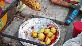 Le marchand ambulant frotte un épi rôti de maïs avec le citron et les épices banque de vidéos