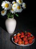 Le margherite alba, margherite bianche naturali stanno in una brocca bianca del gesso, accanto ad un piatto con le fragole fresch fotografie stock