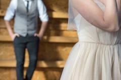 Le marié à l'arrière-plan, la jeune mariée dans le premier plan Image stock