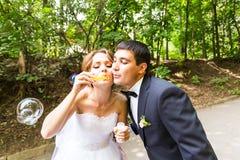 Le marié élégant élégant et la jeune mariée magnifique heureuse ont l'amusement avec le ventilateur de bulle dehors dans le parc Images stock