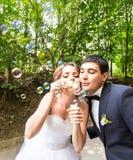 Le marié élégant élégant et la jeune mariée magnifique heureuse ont l'amusement avec le ventilateur de bulle dehors dans le parc Photographie stock