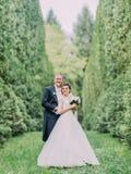 Le marié étreint le brife de retour dans le jardin avec de hauts buissons Photo libre de droits