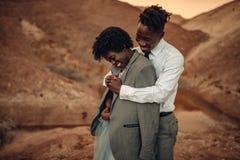 Le marié étreint sa jeune mariée habillée dans sa veste en canyon au coucher du soleil a Image libre de droits