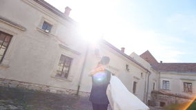 Le marié amoureux prend la jeune mariée dans des ses bras et tournoie son rond dans les rues du vieux château banque de vidéos