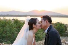 Le marié asiatique embrasse sa jeune mariée contre la scène de coucher du soleil Image stock