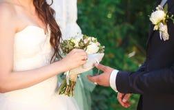 Le marié atteint la jeune mariée image stock