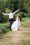 Le marié attrape la jeune mariée Image libre de droits