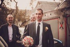 Le marié avec le meilleur homme et les garçons d'honneur vont chez la jeune mariée au mariage Image stock