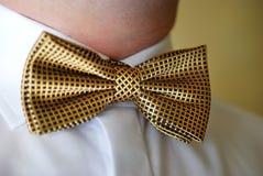 Le marié avec le plan rapproché a façonné le bowtie d'or et la chemise blanche photo stock