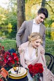 Le marié beau étreignant sa jeune mariée par les shooulders à la table de fête Mariage d'automne dessin-modèle Photos libres de droits