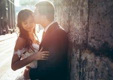 Le marié beau embrasse sa jeune mariée avec du charme dans le front au fond du coucher du soleil Verticale extérieure Image libre de droits