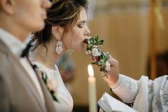 Le marié beau et la belle jeune mariée dans l'église avec le prêtre exécutent images stock
