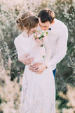 Le marié beau tient doucement le bouquet se tenant arrière de jeune mariée dans le jardin de floraison de ressort Images libres de droits