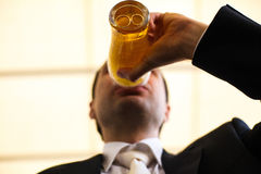 Le marié boit de la bière d'un verre avec des anneaux de mariage Photos libres de droits