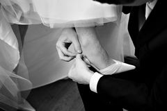 Le marié boutonne la mariée de chaussures Photo stock