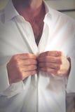 Le marié boutonne sa chemise avant le mariage Image stock