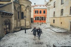 Le marié chic et sa jeune mariée magnifique posent dehors dans des manteaux d'hiver photos stock