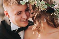 le marié d'étage de robe de couples de mariée remet la fixation regardant la verticale procès se reposant romantique au blanc s'u Photographie stock libre de droits