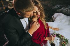 le marié d'étage de robe de couples de mariée remet la fixation regardant la verticale procès se reposant romantique au blanc s'u Image libre de droits