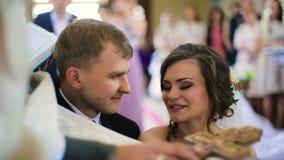 Le marié dans le costume noir tient la jeune mariée que le tenderand de main du ` s indique la promesse banque de vidéos