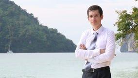 le marié dans des pantalons noirs tient des bras de croisement sur la plage clips vidéos