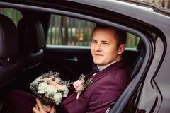 Le marié dans le costume violet en pastel s'assied sur le siège arrière image libre de droits