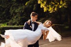 Le marié de jeunes tourbillonne la jeune mariée élégante en parc Photo libre de droits