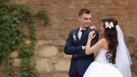 Le marié de sourire beau et sa jeune mariée avec du charme de brune avec l'orchidée dans les cheveux regardent l'un l'autre et po clips vidéos