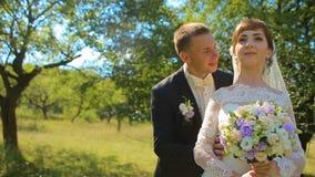 Le marié donne à la jeune mariée un bouquet de sa position sur un genou sur la nature clips vidéos