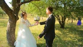 Le marié donne à la jeune mariée un bouquet de sa position sur un genou sur la nature banque de vidéos