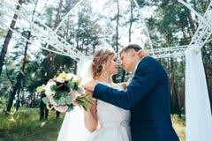 Le marié embrasse la jeune mariée à la cérémonie de mariage Les jeunes mariés dans des robes de mariage sur le fond naturel Photo libre de droits