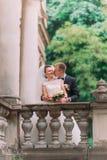 Le marié embrasse la jeune mariée dans la joue tout en se tenant derrière la barrière de la vieille maison Photos libres de droits