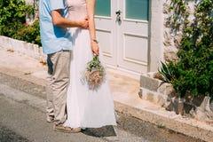 Le marié embrasse la jeune mariée dans la vieille ville Épouser dans Montene Photographie stock libre de droits
