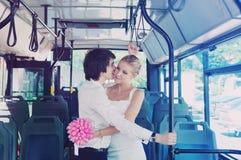 Le marié embrasse la jeune mariée dans le transport en commun Bus bleu Image stock