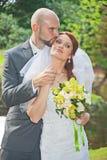 Le marié embrasse la jeune mariée en parc Images libres de droits