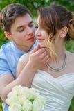 Le marié embrasse la jeune mariée sur un fond des feuilles vertes dans le PS Photos stock
