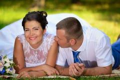 Le marié embrasse la jeune mariée sur une épaule photographie stock libre de droits
