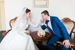 Le marié embrasse la main de la jeune mariée dans un bel intérieur photos stock