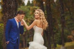 Le marié embrasse la main de la jeune mariée en parc Photo libre de droits