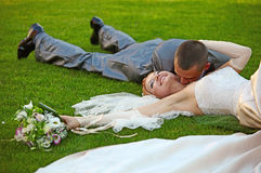 Le marié embrasse la mariée se trouvant sur une herbe photo stock