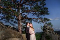 Le marié embrasse le chef de la jeune mariée brillante tandis qu'ils se tiennent sur la roche photos stock