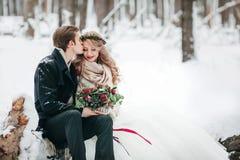 Le marié embrasse sa jeune mariée sur le temple sur le fond du mariage neigeux d'hiver de forêt dessin-modèle Photo stock
