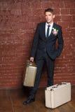 Le marié est un mur de briques avec des valises Photos stock