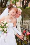 le marié et la fiancée en parc accrochent une serrure sur le pont de Photographie stock