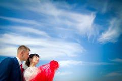 Le marié et la jeune mariée contre le ciel bleu Photographie stock