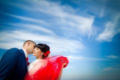 Le marié et la jeune mariée contre le ciel bleu Photographie stock libre de droits